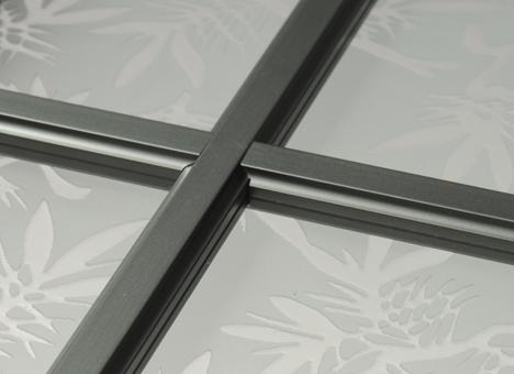 Assemblage de profils décoratifs par fraisage à l'intérieur d'un double ou triple vitrage. Ils se déclinent en différentes largeurs, différents aspects (laiton, blanc, gris plomb), ils peuvent aussi être filmés ou laqués dans une multitude de RAL.